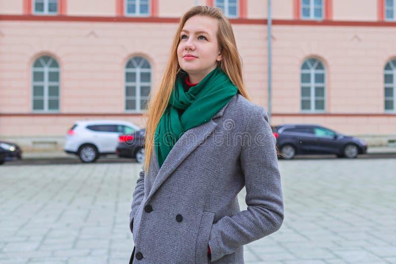 Glückliches Mädchen in einem grauen Mantel mit dem roten Haar gehend hinunter die Straße stockbild