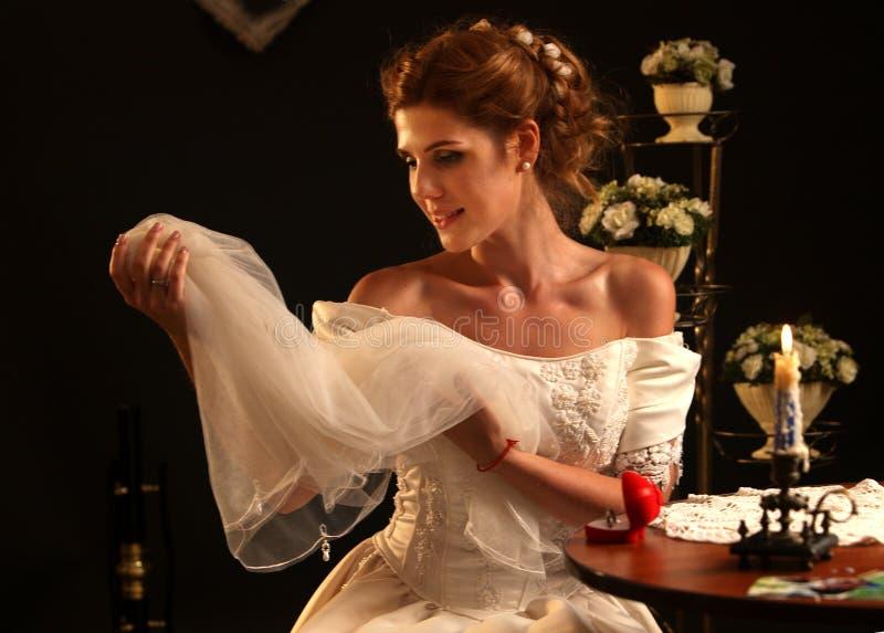 Glückliches Mädchen in einem Hochzeitskleid sitzt bei Tisch stockfotografie