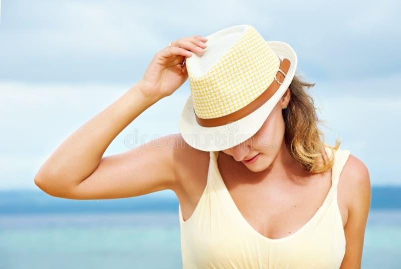Glückliches Mädchen in einem Hut, der auf Strand stillsteht stockbild