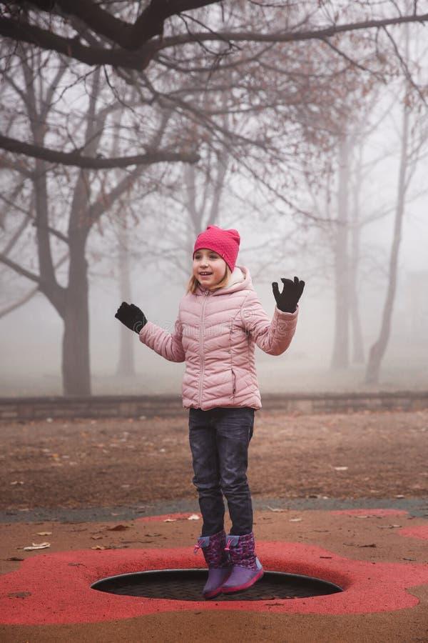 Glückliches Mädchen in einer rosa Jacke, die draußen auf die Trampoline in Park springt Herbst, nebelhafter Wald lizenzfreie stockbilder