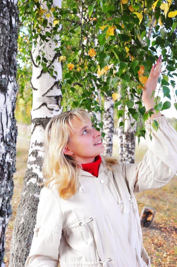 Glückliches Mädchen an einer weißen Birke stockbild