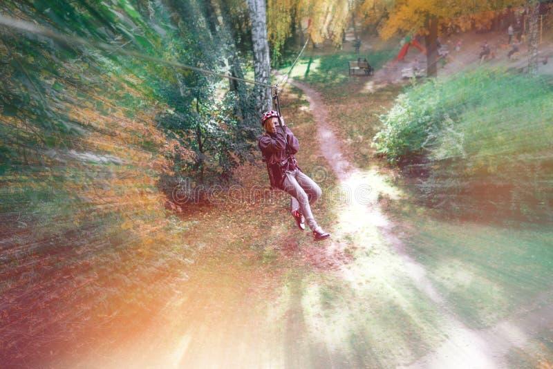 Glückliches Mädchen, Frau, kletternder Gang in einem Abenteuer, Seilstraße, Versicherung, Anziehungskraft, Vergnügungspark, aktiv stockbild