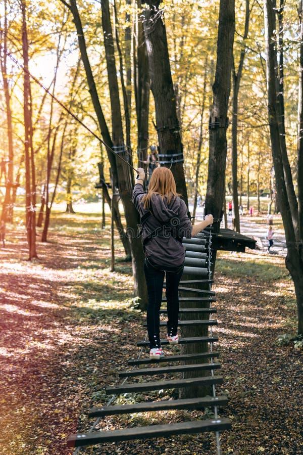 Glückliches Mädchen, Frau, kletternder Gang in einem Abenteuer, Seilstraße, Versicherung, Anziehungskraft, Vergnügungspark, aktiv stockfotos