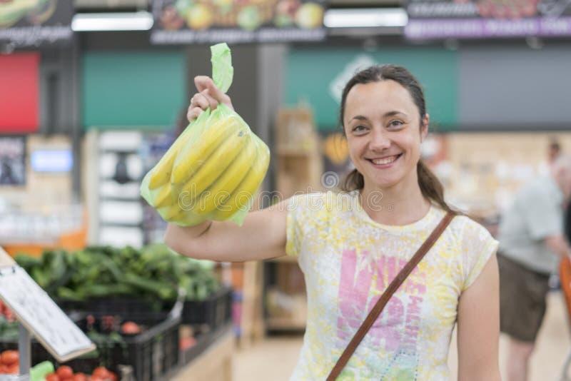 Glückliches Mädchen gekauft Bananen im Speicher Lächelnde Frau mit Bananen in der Hand blurry stockfoto