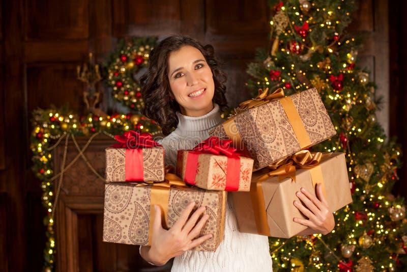 Glückliches Mädchen hält viele Weihnachtsgeschenke stockfotografie