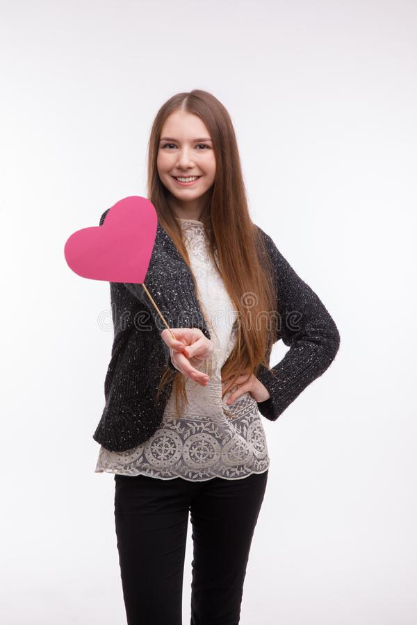 Glückliches Mädchen, Herz der Griffe in der Hand auf Stock und Lächeln Getrennt stockfotos
