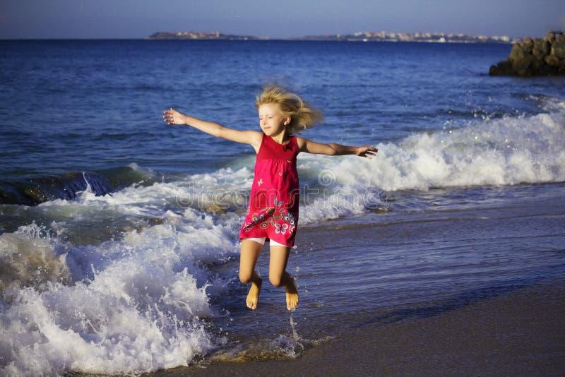 Glückliches Mädchen im farbigen Kleid, das auf die Wellen auf dem Strand springt stockfotografie