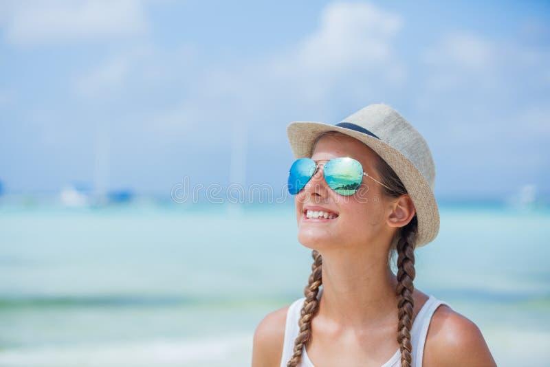 Glückliches Mädchen im Hut und in der Sonnenbrille auf Strand Reisenkoffer mit Meerblick nach innen lizenzfreie stockbilder