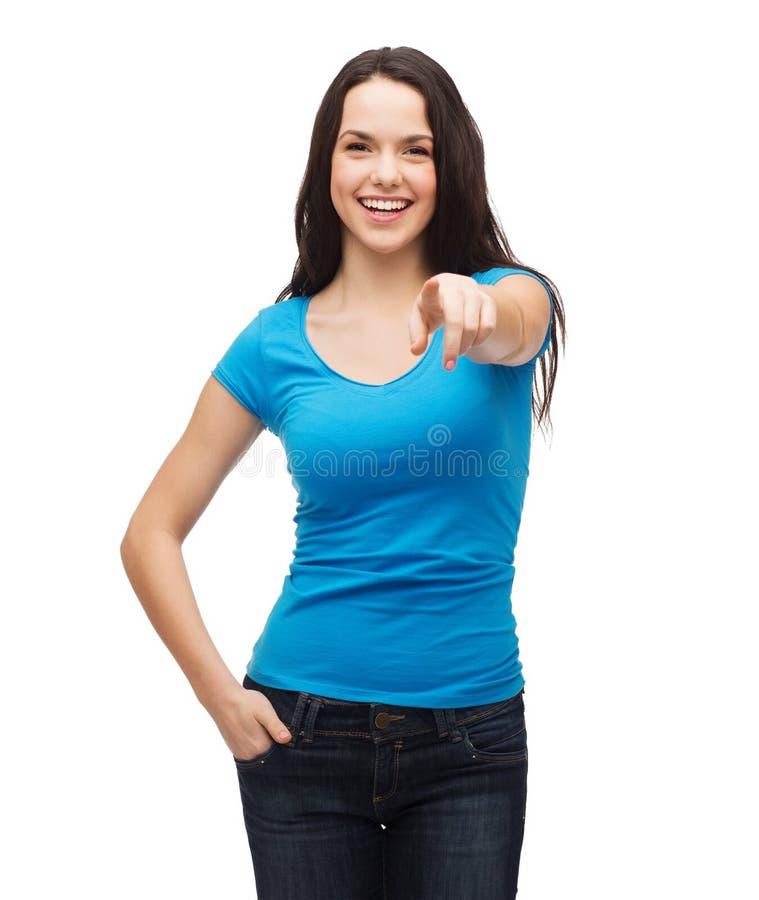 Glückliches Mädchen im leeren blauen T-Shirt zeigend auf Sie stockbild