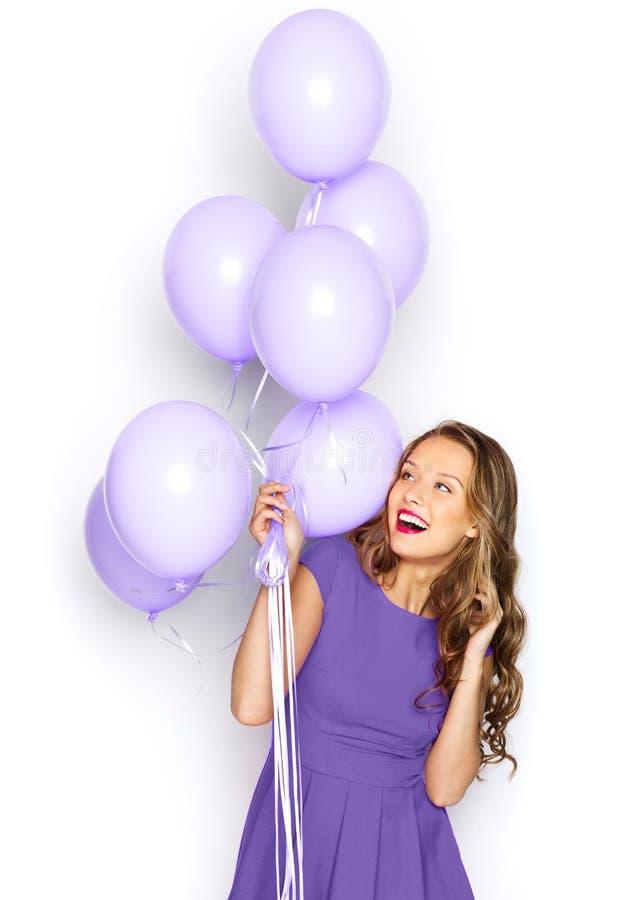 Glückliches Mädchen im ultravioletten Kleid mit Ballonen lizenzfreie stockbilder