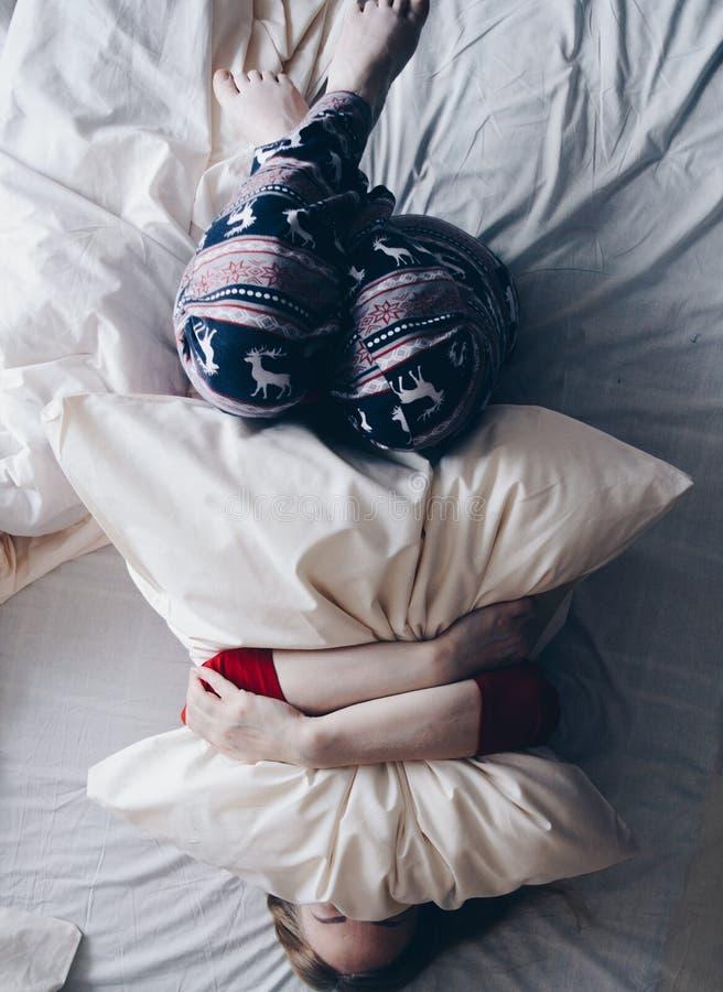 Glückliches Mädchen im Winter kleidet auf dem weißen Bett, das ein Kissen umarmt lizenzfreies stockbild