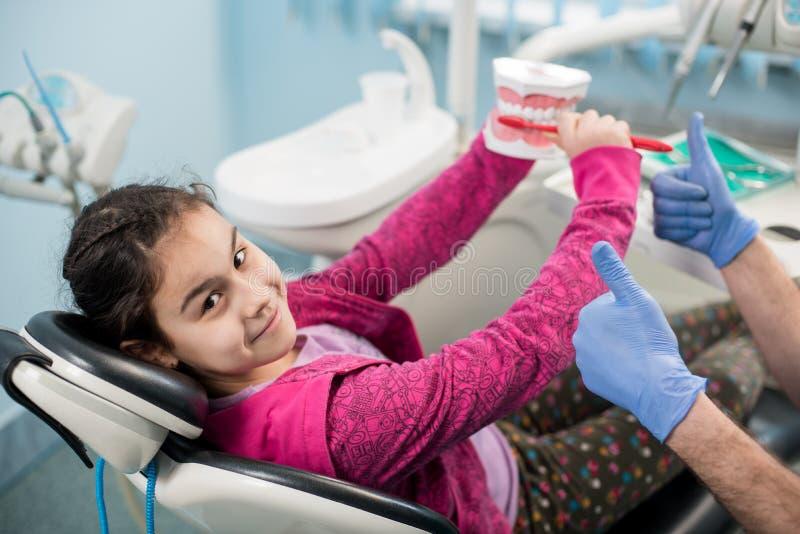 Glückliches Mädchen im Zahnarztstuhl erziehend über richtiges Zähneputzen in der zahnmedizinischen Klinik Zahnheilkunde, Mundhygi lizenzfreies stockfoto