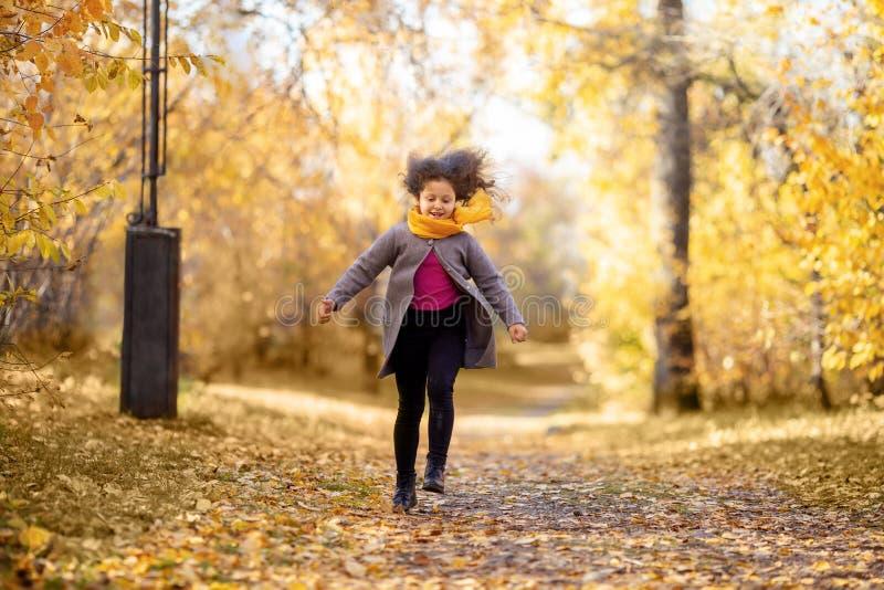 Glückliches Mädchen läuft in Herbstpark stockbilder
