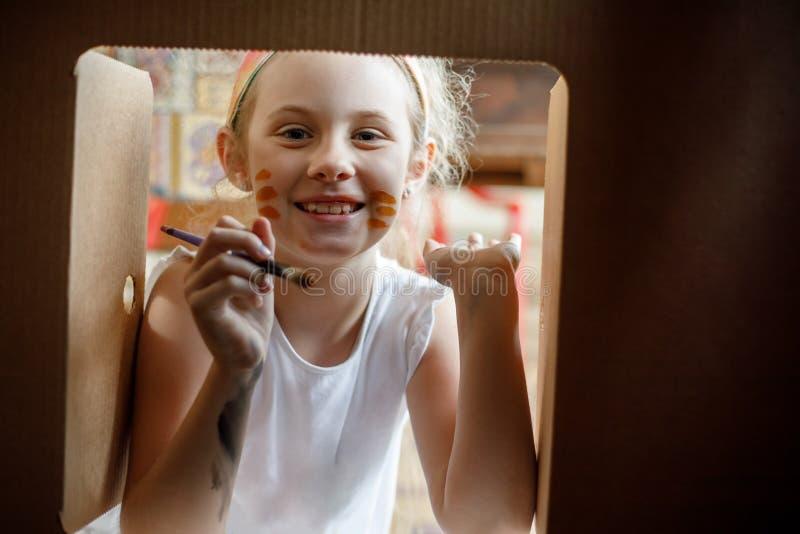 Glückliches Mädchen malt auf ihrem Gesicht, das durch Fenster des Papphauses schaut stockfotos