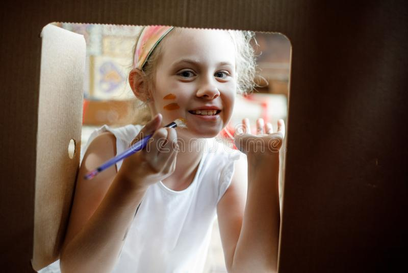 Glückliches Mädchen malt auf ihrem Gesicht, das durch Fenster des Papphauses schaut lizenzfreies stockfoto