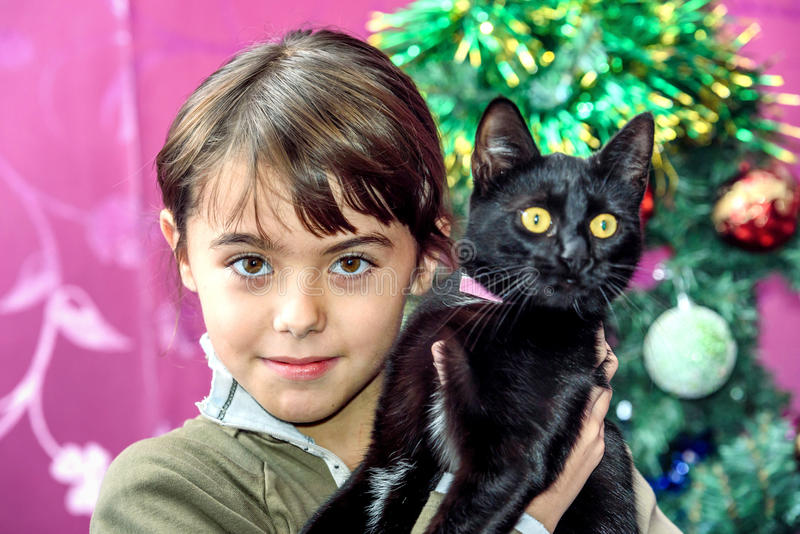 Glückliches Mädchen mit acht Jährigen mit schwarzer Katze für Weihnachtsgeschenk lizenzfreie stockfotos