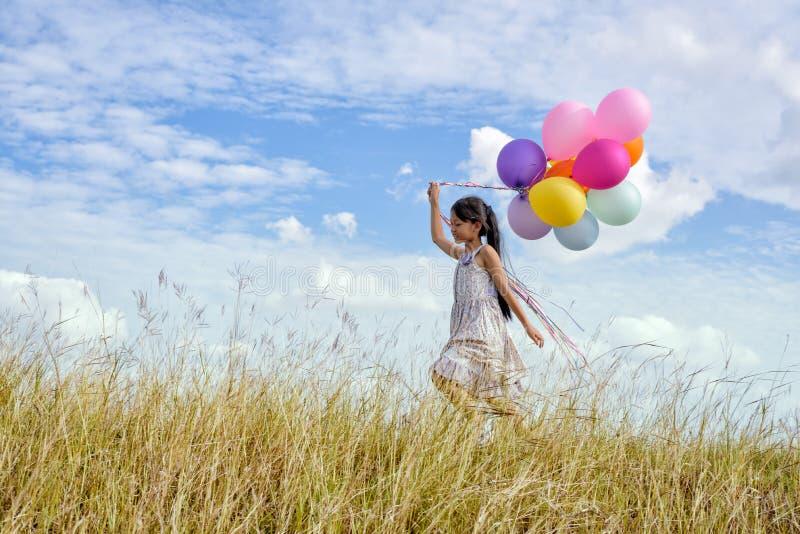 Glückliches Mädchen mit bunten Ballonen stockbild