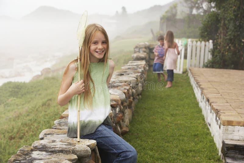 Glückliches Mädchen mit dem Fischernetz, das auf Steinwand am Yard sitzt lizenzfreies stockfoto