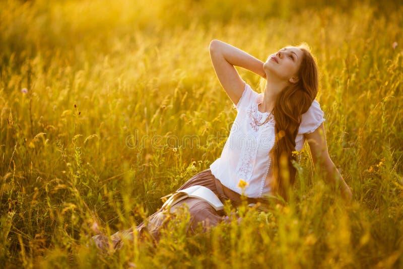 Glückliches Mädchen mit einem Buch träumend über etwas stockbild
