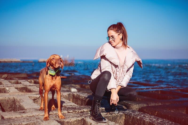 Glückliches Mädchen mit einem Hund in dem Meer stockfoto