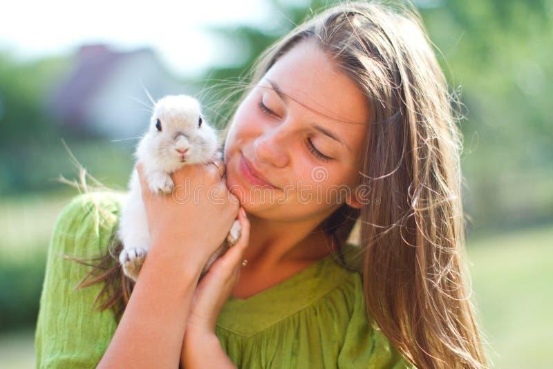 Glückliches Mädchen mit einem Kaninchen in ihren Armen lizenzfreie stockfotografie