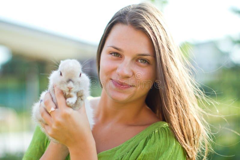 Glückliches Mädchen mit einem Kaninchen in ihren Armen lizenzfreies stockbild