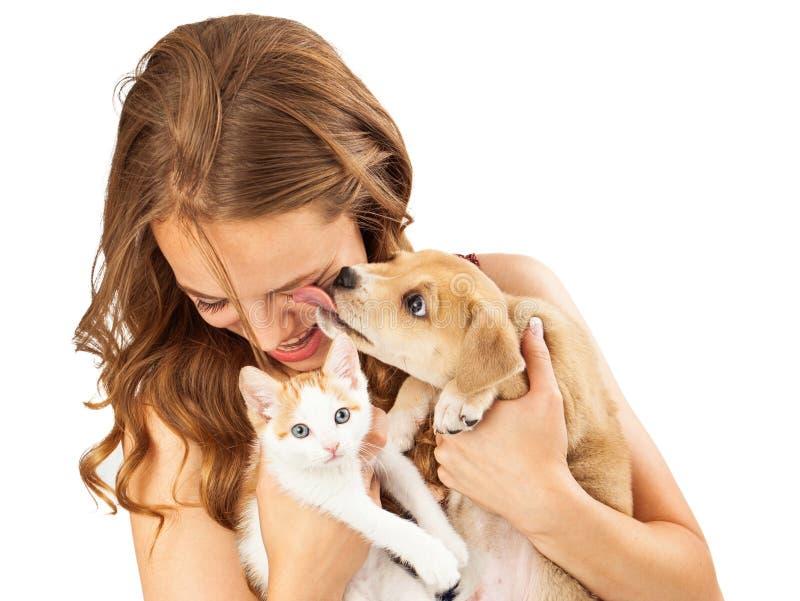 Glückliches Mädchen mit Kätzchen und liebevollem Welpen lizenzfreies stockfoto