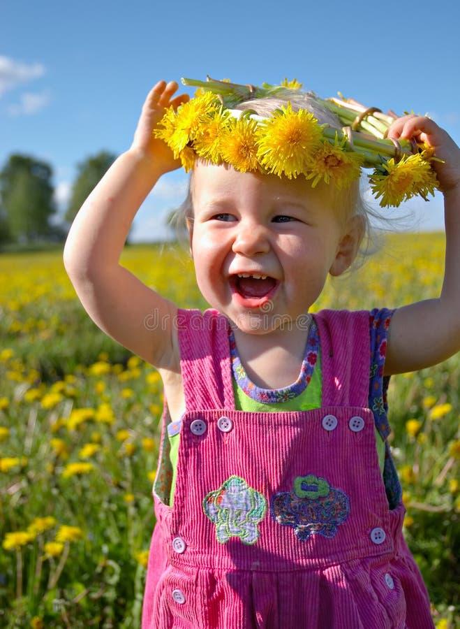 Glückliches Mädchen mit Löwenzahn Wreath lizenzfreie stockfotografie