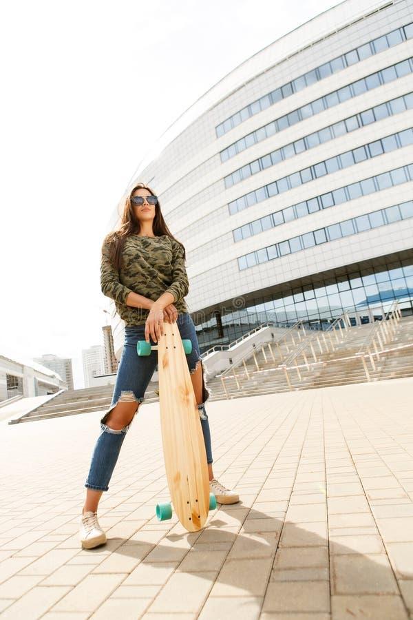 Glückliches Mädchen mit longboard Skateboard stockfoto