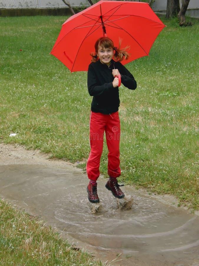 Glückliches Mädchen mit Regenschirmsprung auf Pfützen des Wassers lizenzfreies stockfoto