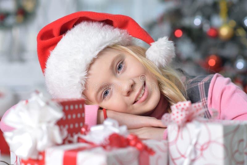 glückliches Mädchen in Sankt-Hut, der mit Weihnachtsgeschenken sitzt stockfotografie