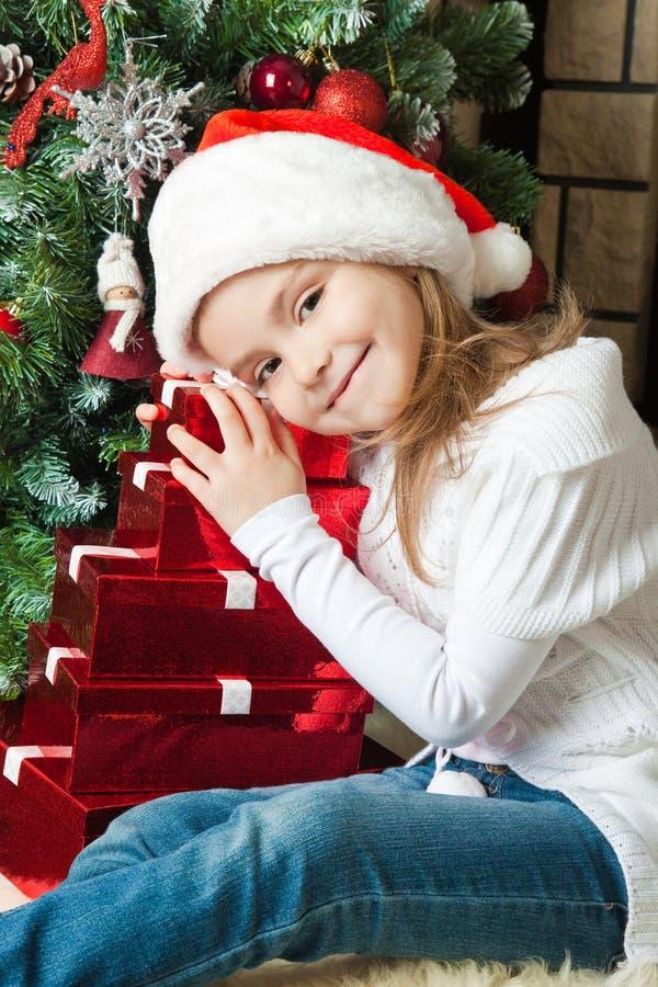 Glückliches Mädchen in Sankt-Hut mit Geschenken nähern sich Weihnachtsbaum stockfotografie
