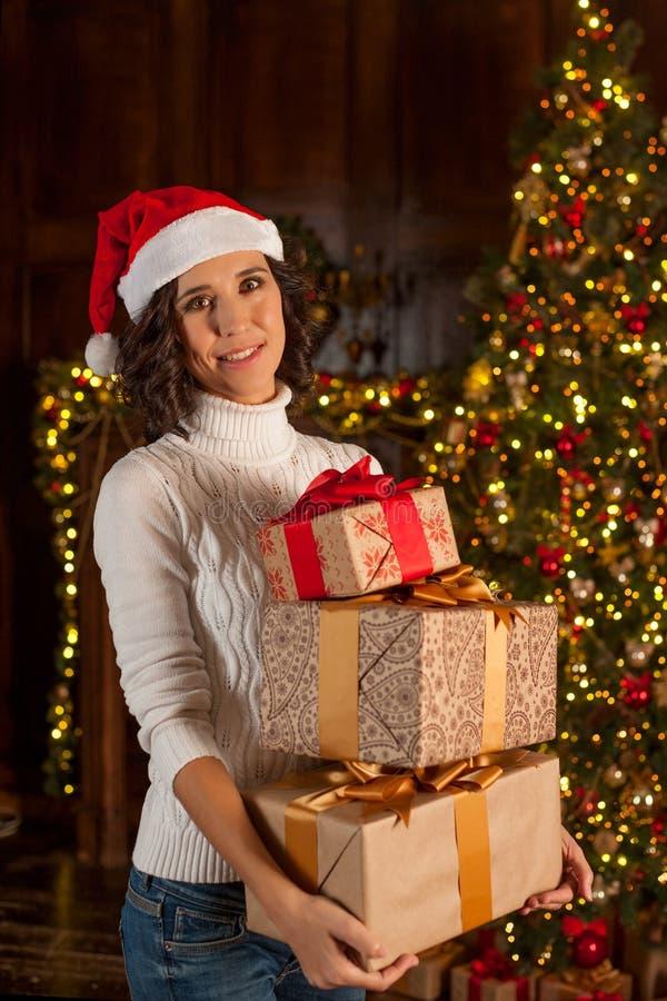 Glückliches Mädchen in Sankt-` s Hut mit vielen Weihnachtsgeschenken stockbilder