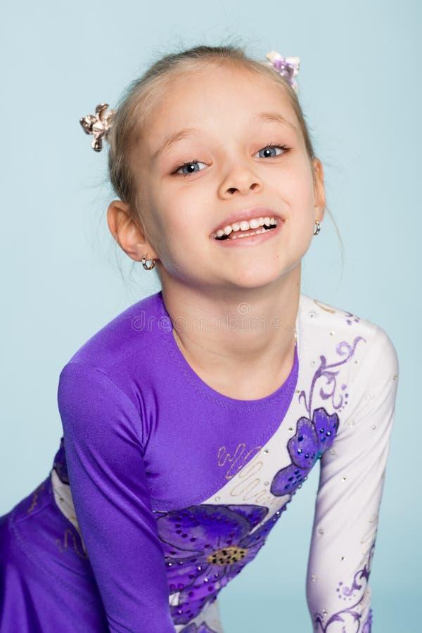 Glückliches Mädchen sieben Jahre auf einem blauen Hintergrund lizenzfreies stockbild