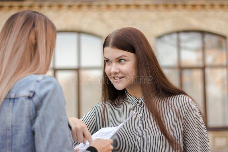 Glückliches Mädchen steht nahe der Universität und dem Blick am Erwachsenen mit Papier stockfoto