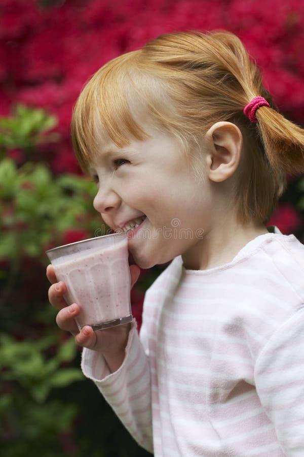 Glückliches Mädchen trinkender Smoothie am Yard lizenzfreie stockbilder