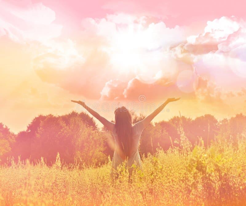 Glückliches Mädchen, welches das Glück auf sonniger Wiese genießt stockfoto
