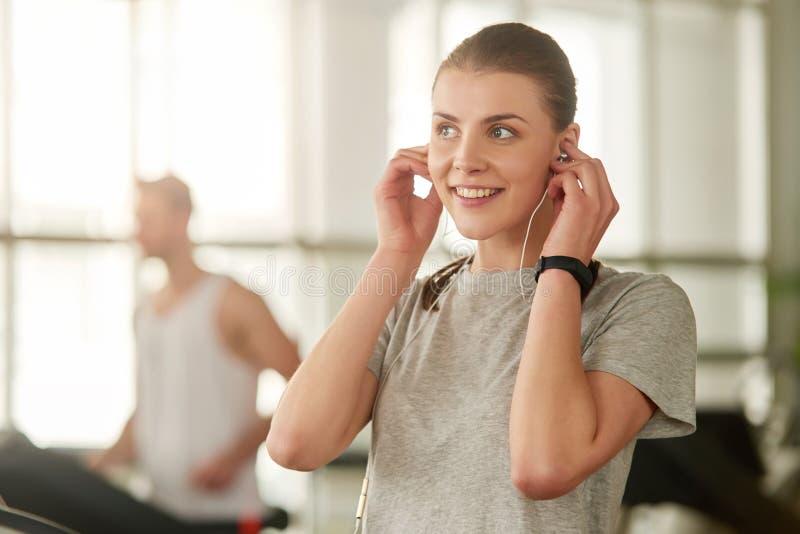 Glückliches Mädchen, welches das Hören Musik in der Turnhalle genießt stockbilder