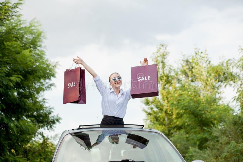 Glückliches Mädchen, welches die Einkaufspakete in der Autoluke, Konzept von Rabatten und den Einkauf hält stockbild