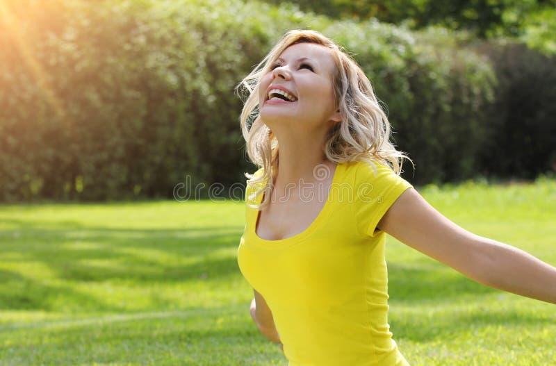 Glückliches Mädchen, welches die Natur auf grünem Gras genießt.  Schöne junge Frau, die mit den Armen ausgestreckt lächelt stockfoto