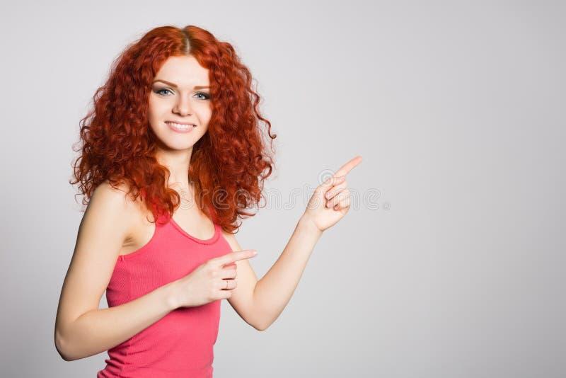 Glückliches Mädchen zeigt Finger auf die Seite lizenzfreie stockfotos