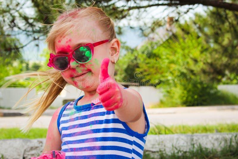Glückliches Mädchen zeigt Klasse mit holi Farbe stockfotografie