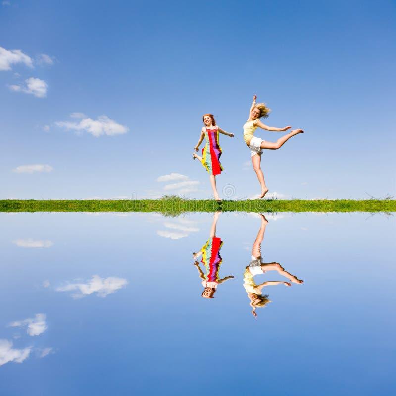 Glückliches Mädchen zwei, das zusammen auf grüne Wiese springt stockfotos