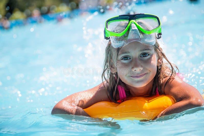 Glückliches Mädchenkind, das im Pool an einem sonnigen Tag spielt Nettes kleines Mädchen, das Feiertagsferien genießt stockfotos