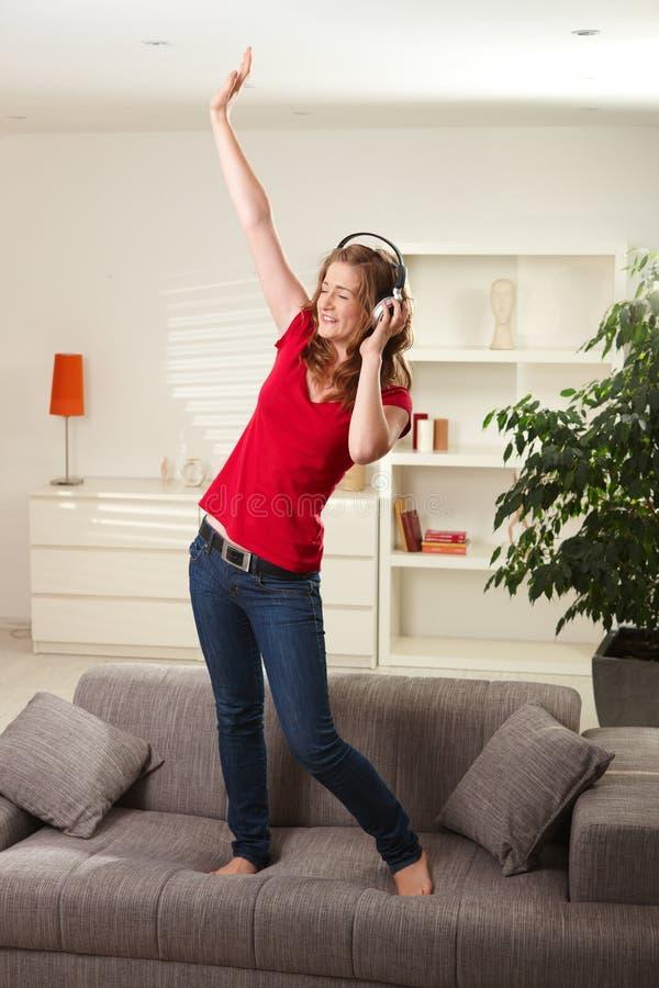 Glückliches Mädchentanzen auf Couch mit Kopfhörern stockbild