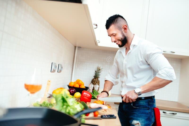 Glückliches Mannausschnittgemüse für Salat oder Suppe Junger Fachmann kleidete gut den Koch, der Lebensmittel in der neuen Küche  stockfotos