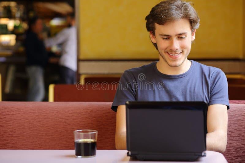 Glückliches Manngraseninternet auf einem Laptop in einem Restaurant lizenzfreie stockfotografie