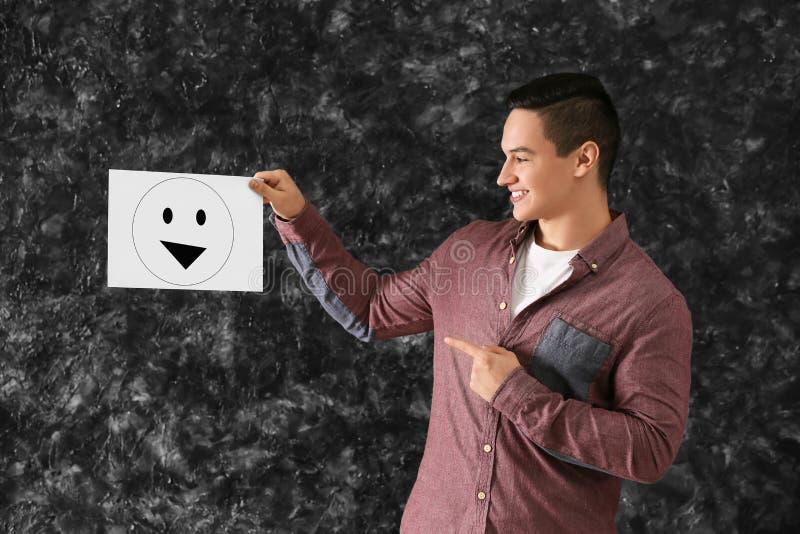 Glückliches Mannholdingblatt papier mit gezogenem Emoticon auf grauem Hintergrund lizenzfreies stockfoto