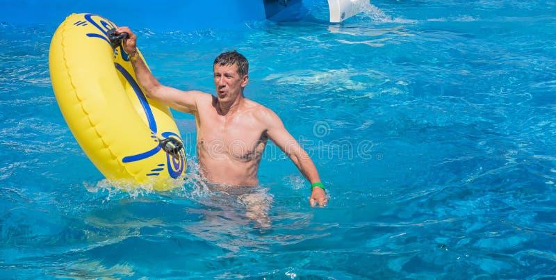 Glückliches Mannverlassen einen Swimmingpool lizenzfreie stockfotografie