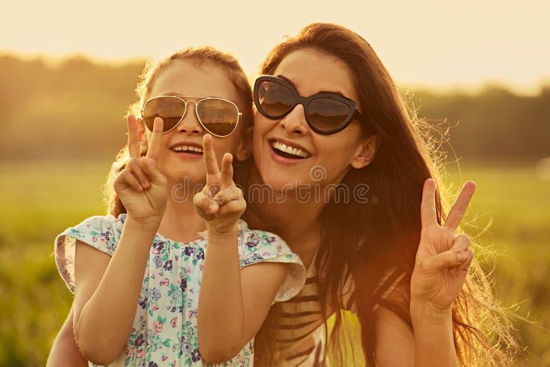 Glückliches Modekindermädchen, das ihre Mutter in der modischen Sonnenbrille umfasst und Siegeszeichen durch zwei Finger auf Natu lizenzfreies stockfoto